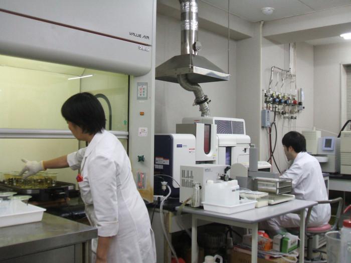 重金属分析状況 (左)ドラフト内での前処理、塩酸と硝酸との混酸による分解 (右)原子吸光光度計での定量分析